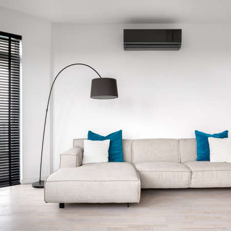 Simple style living room with white walls, windows with black blinds and with beige corner sofa with blue pillows under air conditioner and lamp