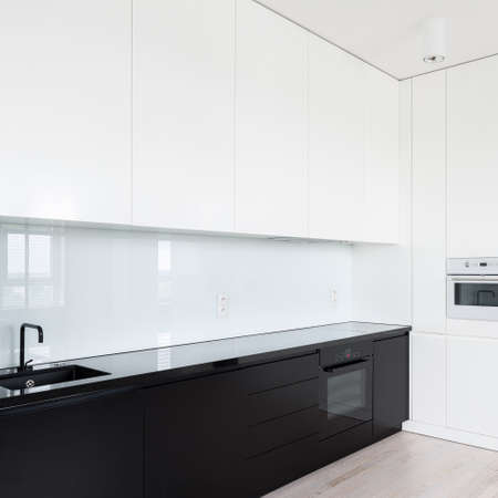 Simple and elegant black and white kitchen with many drawers and cupboards and glass backsplash