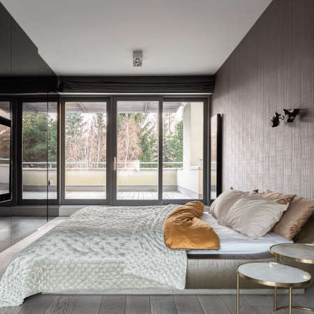 Morning in luxury bedroom with big and comfortable bed, stylish wallpaper and window wall to balcony