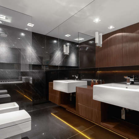 Fancy designed bathroom with elegant wooden furniture, luxury marble wall and floor tiles and classic white two washbasins, toilet and bidet