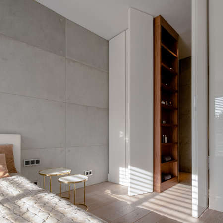 Stylish bedroom with concrete wall and with bathroom with wardrobe behind open white doors high to the ceiling Banque d'images