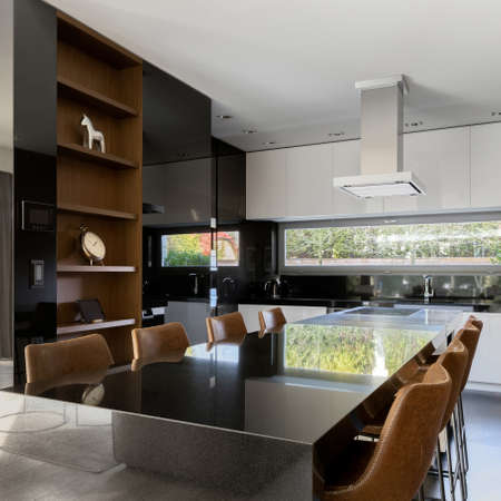Stylish and long dining table with eight modern chairs in elegant black, white and wooden kitchen with window