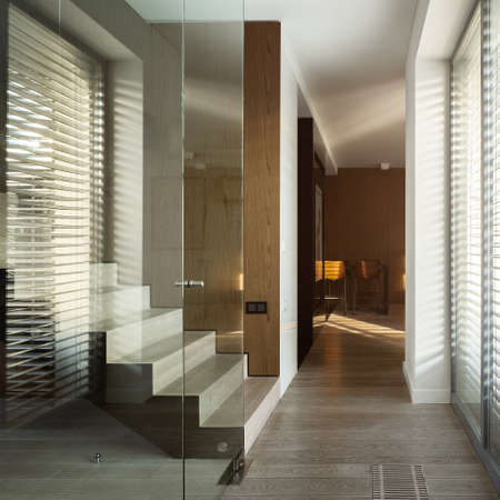 Modern wooden stairs behind glass wall in stylish home corridor with big window Stock Photo