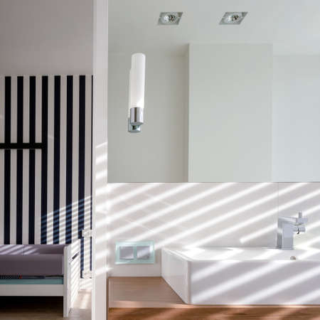 Simple white bathroom with big mirror above washbasin next to child room with wallpaper in black and white stripes Imagens