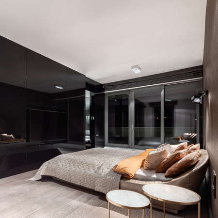 Luxury bedroom with black mirrored wall, big television screen and fancy bed at night with lights on