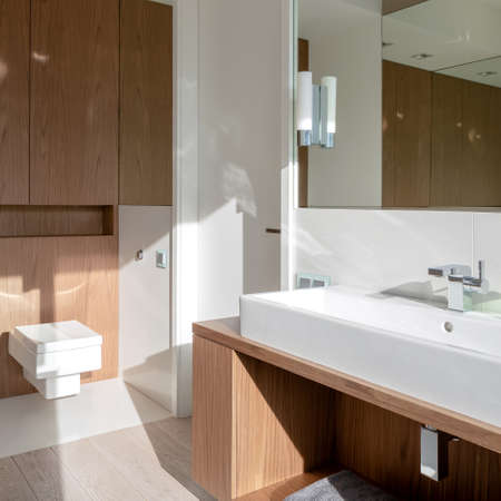 Simple bathroom with long washbasin, square toilet and wooden furniture and wooden style floor tiles Imagens