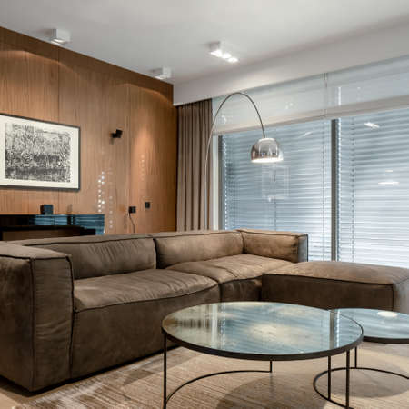 Modern and stylish living room with wooden wall, elegant furniture and new lights on