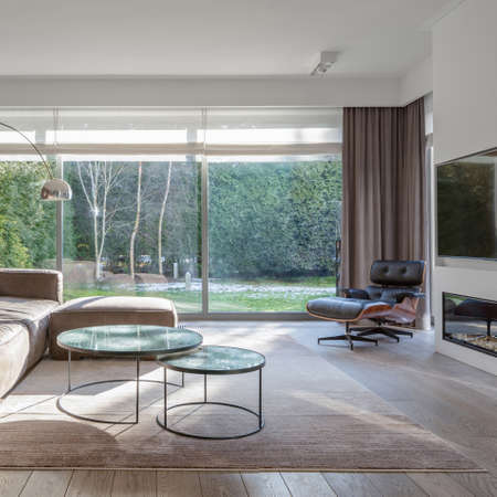 Luxury living room with sofa, tv, armchair and stylish coffee tables in house with big windows and garden view Imagens