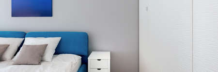 Panorama of simple bedroom with blue bed and art, white bedside table and big white wardrobe
