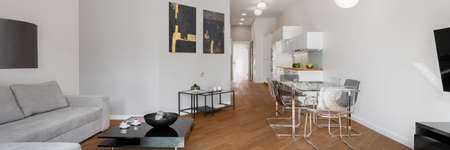 Panorama of spacious and modern apartment with wooden floor and living room with dining area open to kitchen in corridor