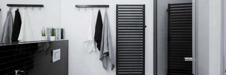 Panorama of simple black and white bathroom interior with decorative black wall heater