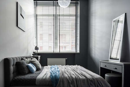 Small and stylish bedroom in gray with big bed, dressing table with mirror and window
