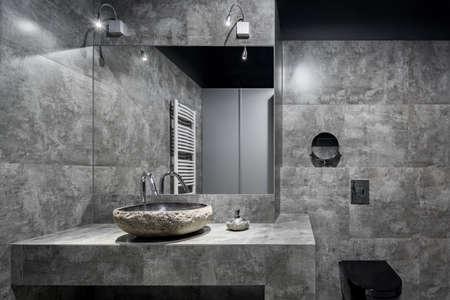 Dark bathroom with gray wall tiles, modern, stone style washbasin and black toilet