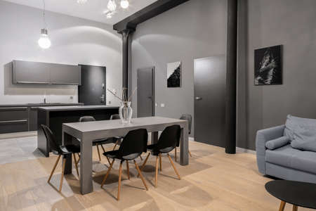 Big gray dining table with six black chairs in modern loft style apartment with dark doors and pillars