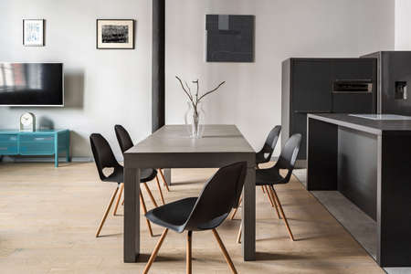 Modern gray dining table with five stylish chairs in loft apartment with wooden floor