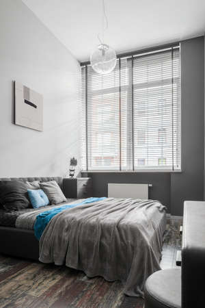 Stylish bedroom in gray with double and comfortable bed and big window
