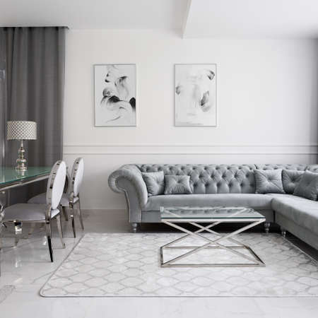 Luxurious and glamor style living room interior with quilted corner sofa, glass coffee and dining tables and fancy chairs
