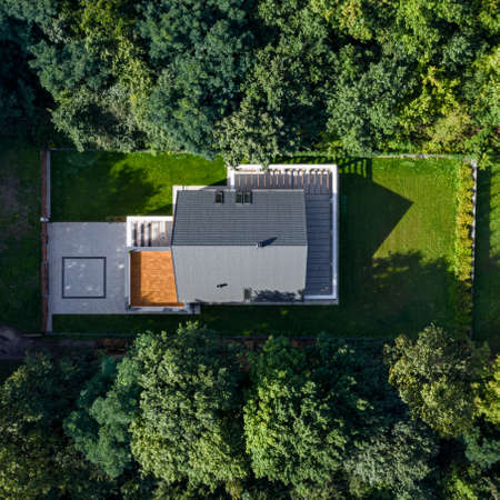 Drone view of modern house with green garden in forest Stockfoto