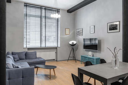 Stylish living room and dining table in modern loft with big window Imagens