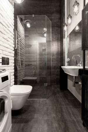 Elegant bathroom with shower behind glass wall, white brick and dark gray tiles Foto de archivo