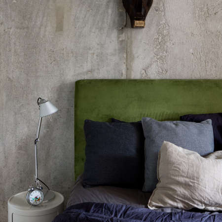Stylish bedroom with concrete wall and small bedside table with lamp next to big bed with velor green headboard