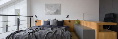 Panorama of modern bedroom on mezzanine with wooden headboard and long wooden desk