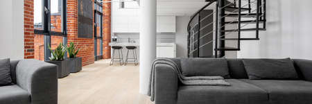 Panorama of modern loft apartment with exposed brick on walls, big windows, black spiral staircase and kitchen open to living room with modern gray couch and armchair