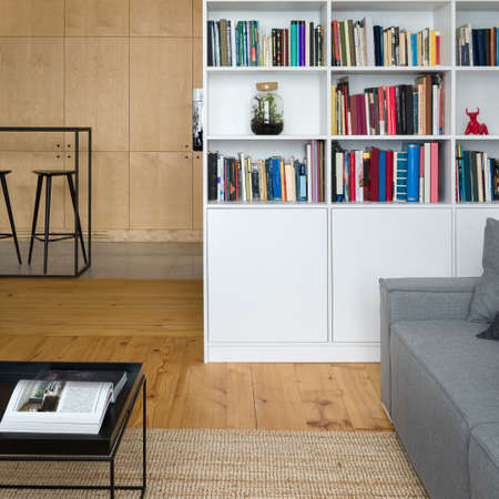 Stylish white bookcase in living room with pine wood floor, square, black coffee table and gray couch