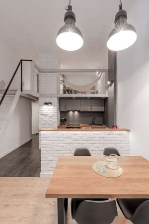 Loft style apartment with white and gray kitchen open to wooden dining table with four, gray chairs under two industrial style lamps