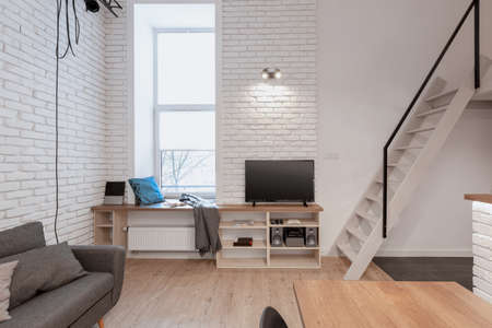 Loft style apartment with stairs to mezzanine from tv room with narrow window and white brick on the walls