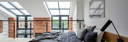 Panorama of simple bedroom on mezzanine in loft style apartment with big windows and exposed red brick on the wall