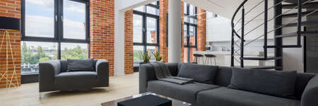 Panorama of simple and bright living room in stylish loft apartment with big windows and red bricks on the walls