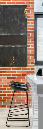 Vertical panorama of exposed red brick on kitchen wall with modern art and white kitchen table with black chairs 免版税图像