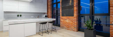 Panorama of stylish kitchen with white furniture and led lights in loft apartment with big windows and brick walls, at night