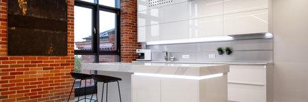 Panorama of luxury white kitchen interior with loft style brick wall and big window