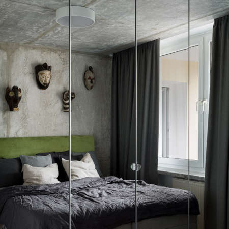 Modern bedroom with exposed concrete on wall and ceiling, decorative masks and mirrors on wardrobe doors
