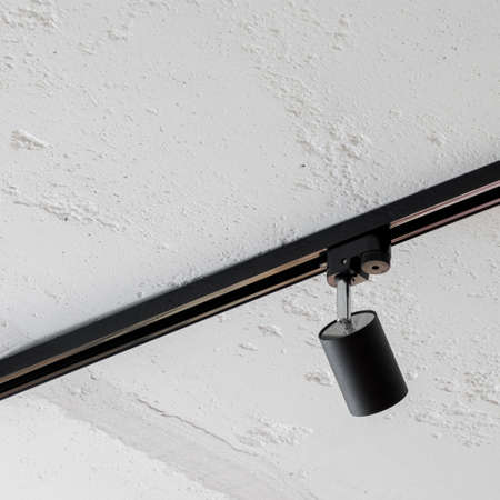 Close-up on modern black lamp on rail to slide on white concrete ceiling