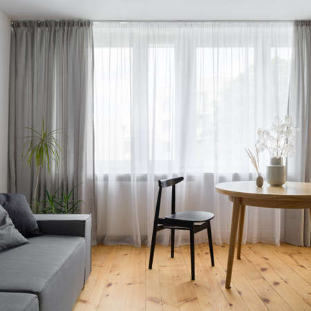 Wooden dining table with nice decorations and black chair in living room with window wall behind white curtains, wooden floor and gray sofa