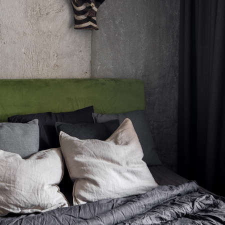 Close-up on bed with green velor headboard in dark bedroom with industrial style concrete wall
