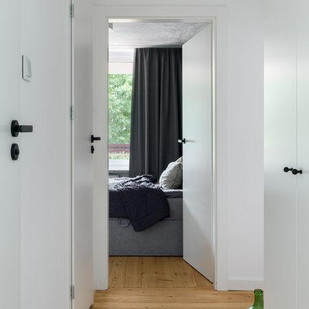 Small and white apartment corridor with many white doors and black door handles, wooden floor and bedroom doors open