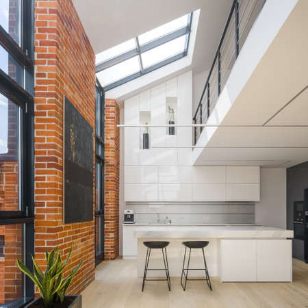 Amazing big windows in loft style apartment with white, spacious and luxury kitchen, exposed red bricks on the walls and mezzanine