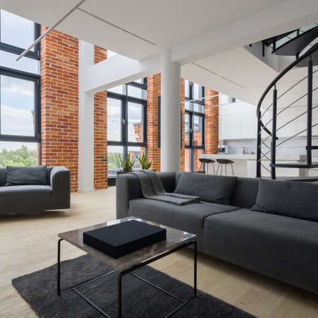 Simple and bright living room in stylish, two-floor loft apartment with amazing, big windows and red bricks on the walls