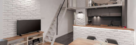 Panorama of modern loft style apartment with mezzanine, white brick on the walls and white stairs