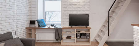 Panorama of living room with stairs and television, window with seat on windowsill and white brick on the walls