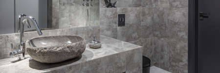 Panorama of modern bathroom with gray wall tiles and stylish, stone like washbasin with silver tap Banque d'images