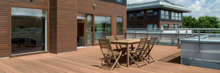 Panorama of spacious wooden terrace with simple wooden furniture in modern building, exterior view