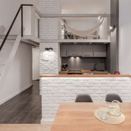Studio apartment with room with hammock on mezzanine above stylish kitchen open to wooden dining table Archivio Fotografico