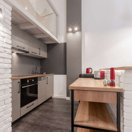 Small and functional kitchen with stylish gray furniture, wooden countertops and shelves and white brick on walls