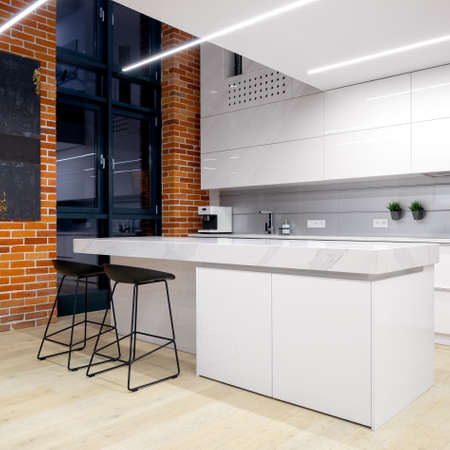 Modern white kitchen with led lighting and with brick wall in loft at night