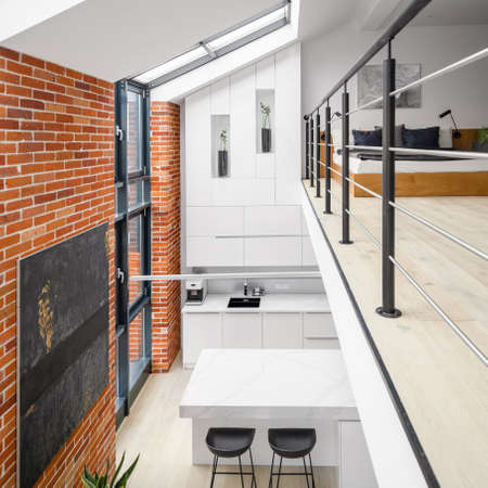 Stylish two-floor loft apartment with exposed red brick on the walls and big windows in kitchen and bedroom on mezzanine floor